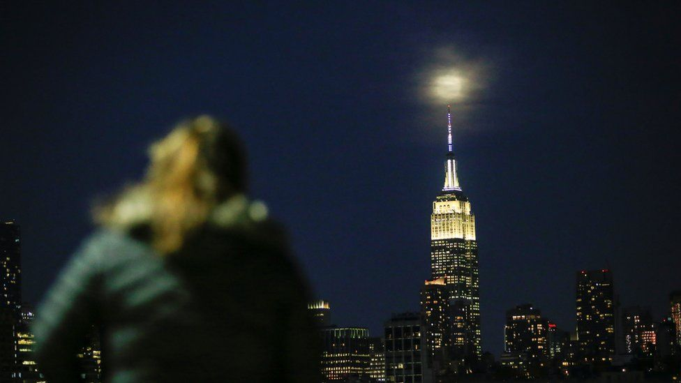 A woman looks at the supermoon in New York