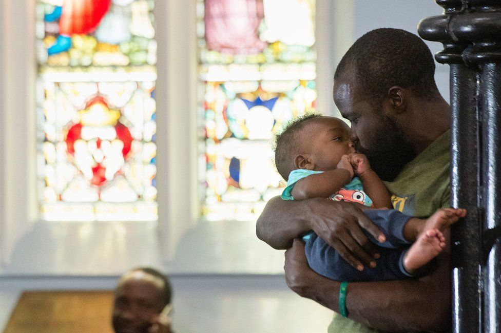 A man cradles and kisses an infant inside a church.