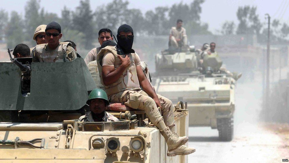 Members of the Egyptian armed forces in armoured vehicles patrolling a street near the town of Sheikh Zuweid, in the northern Sinai peninsula (13 July 2015)