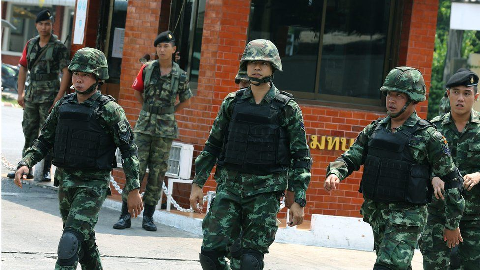 Thai soldiers patrol in front of a military base in Bangkok on 18 April 2016