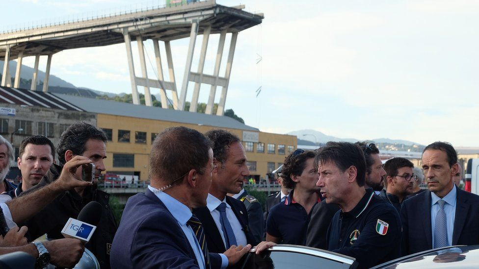 Italian Prime Minister Giuseppe Conte (4th from R) visits the site after a section of the Morandi motorway bridge collapsed in Genoa on August 14, 2018