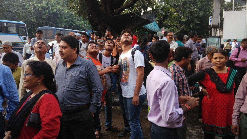 People stand outside their offices after they rushed outdoors following tremors in Kolkata, India, Wednesday, Aug. 24, 2016