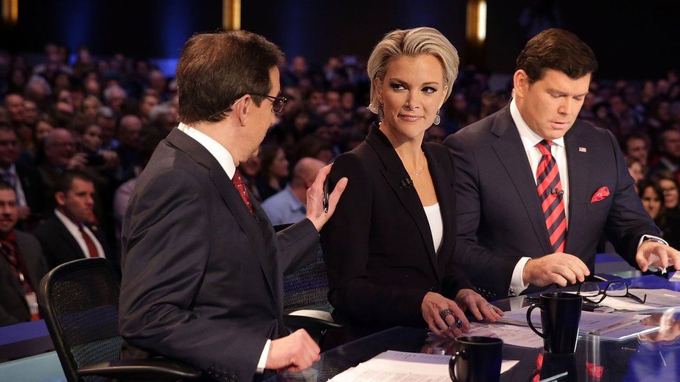 Moderators Chris Wallace (L) pats the shoulder of Megyn Kelly (2nd L) as they wait with Bret Baier (R) for the beginning of the Fox News presidential debate