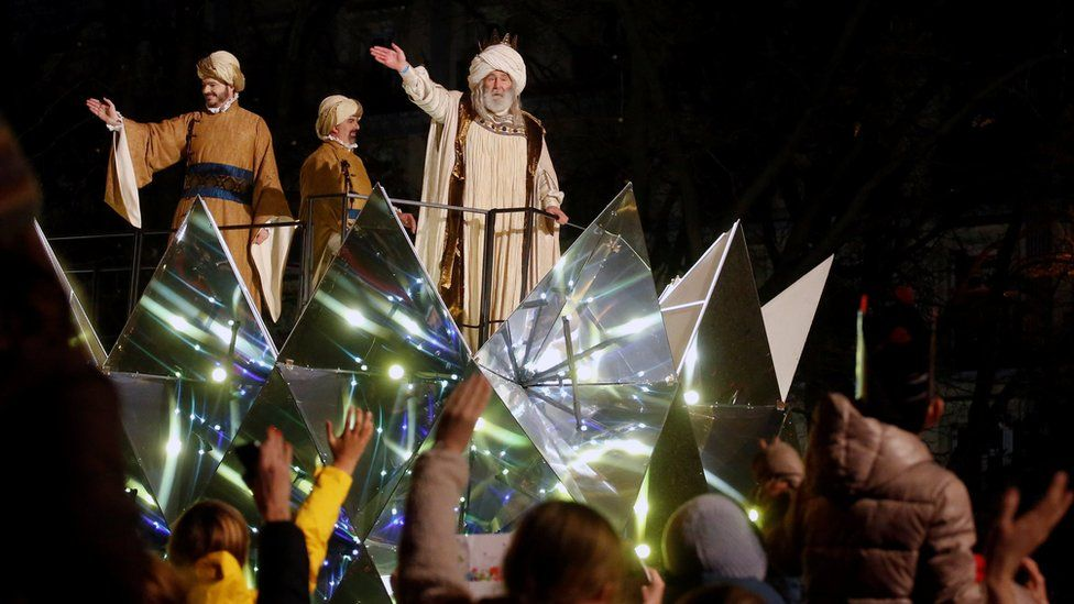 Men dressed as Three Wise Men wave to crowds gathered in Madrid in Spain to celebrate the feast of Epiphany