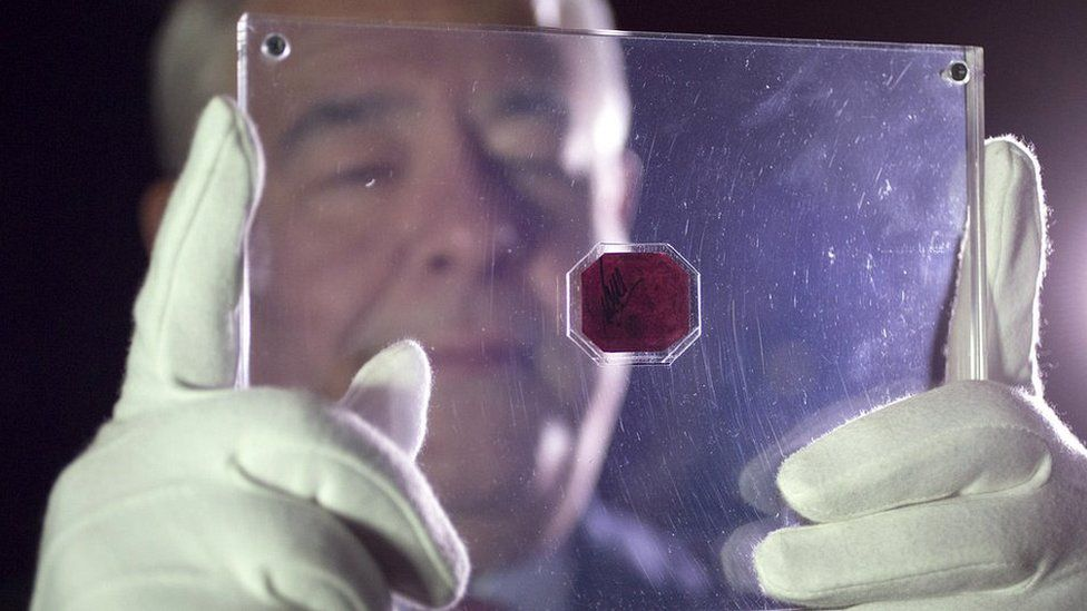 An employee of Sotheby's auction house holds a case containing the sole-surviving 'British Guiana one-cent magenta' stamp dating from 1856, on June 2, 2014 in London, England.