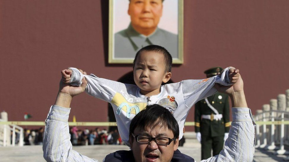 A boy sits on his father's shoulders as they pose for a photograph in front of the giant portrait of late Chinese chairman Mao Zedong on the Tiananmen Gate, in Beijing, China, October 2, 2011.