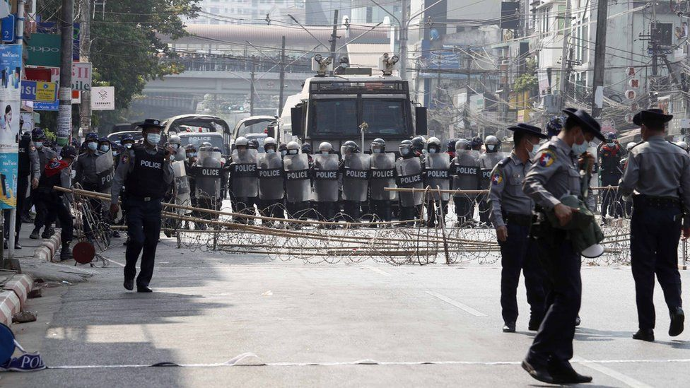 Riot police block a road in Yangon