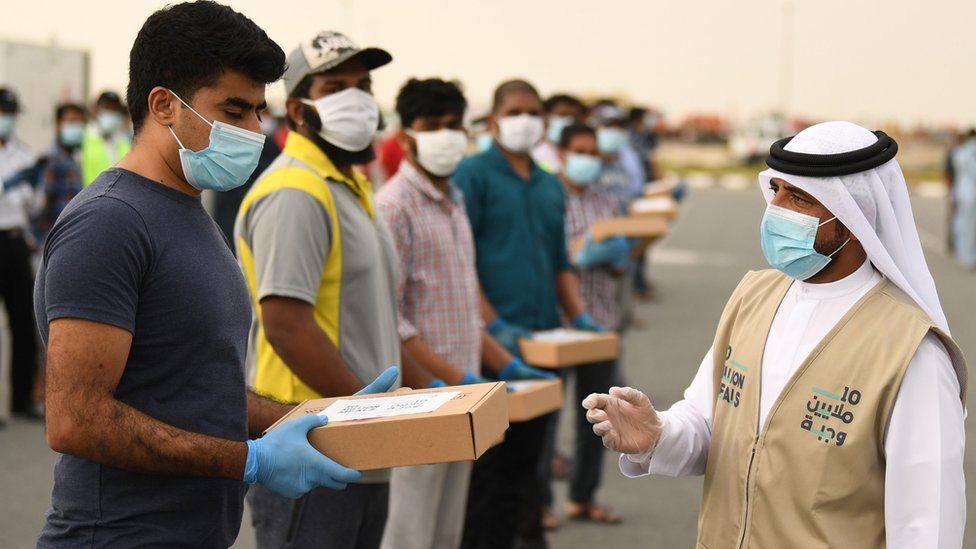 A volunteer distributes iftar meals to migrant workers in Dubai (28 April 2020)