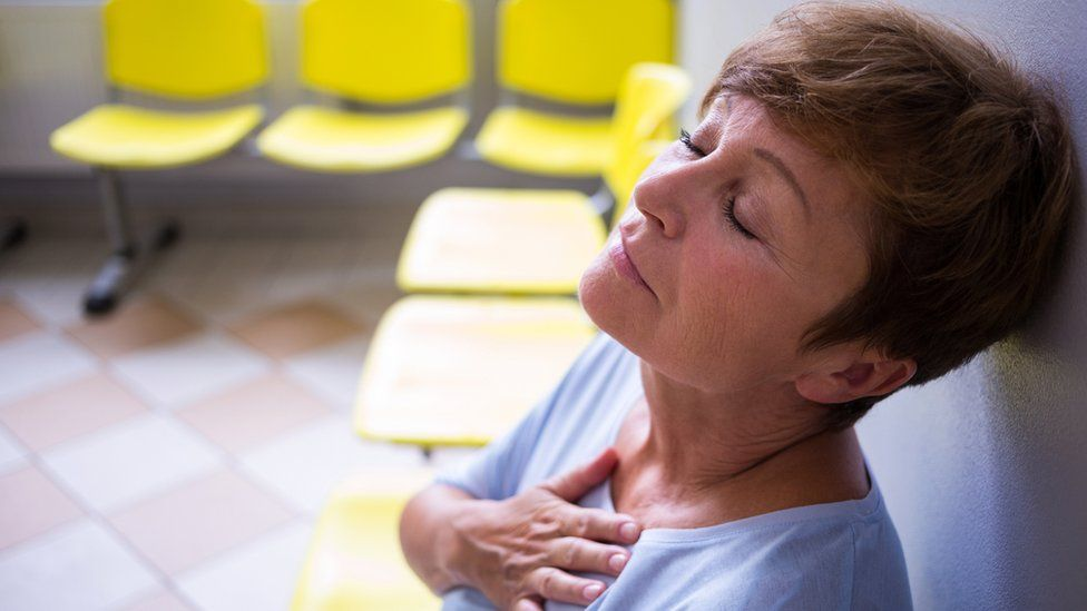 Woman in waiting area holding her chest