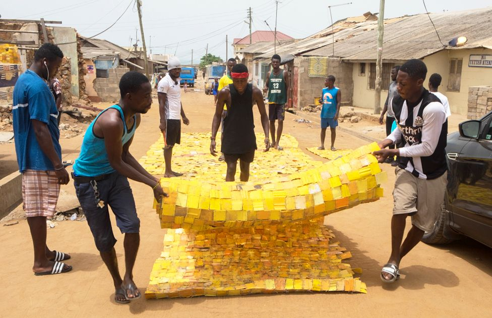 People rolling out yellow tapestry tapestry designed by artist Serge Attukwei Clottey on a road in La - Accra, Ghana