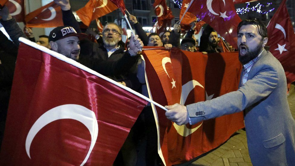 Demonstrators wave flags outside the Turkish consulate in Rotterdam, Netherlands, 11 March 2017