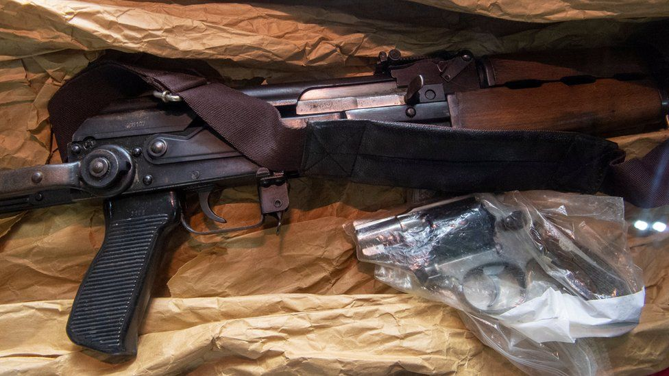 An AK-47 assault rifle and a snub-nosed handgun are displayed atop brown paper