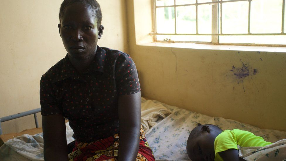 Achan Nighty, 40, sits next to her sleeping son Opio Innocent at hospital