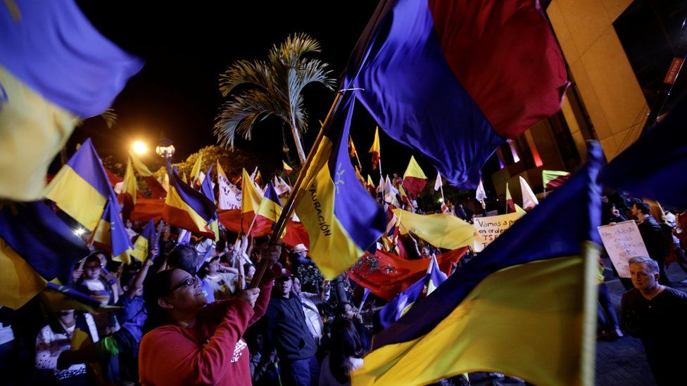 Costa Ricans waving flags and supporting their candidates outside a presidential debate
