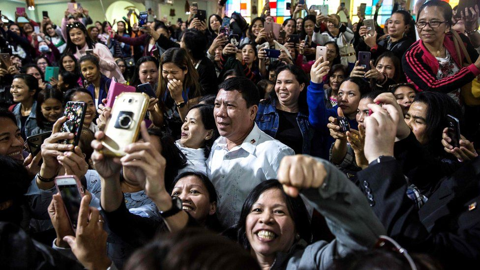 A Rodrigo Duterte impersonator (C), who goes by the name Cresencio Extreme, poses for photos as he attends a church service in the Central district of Hong Kong, 3 February 2019