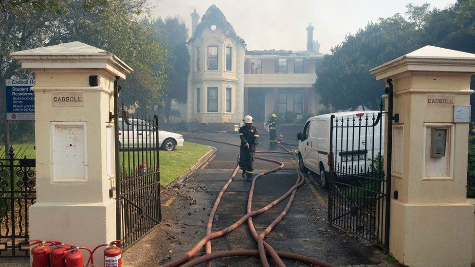 Firefighters check a burnt house, used as a University of Cape Town students' residence, as a forest fire burns out of control on the foothills of Table Mountain