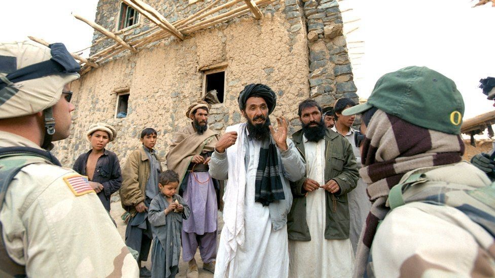 An Afghan interpreter (right) helps an American soldier to question local residents in Afghanistan. File photo