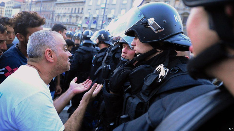 Migrants plead with police officers outside Keleti station in Budapest. 2 Sept 2015
