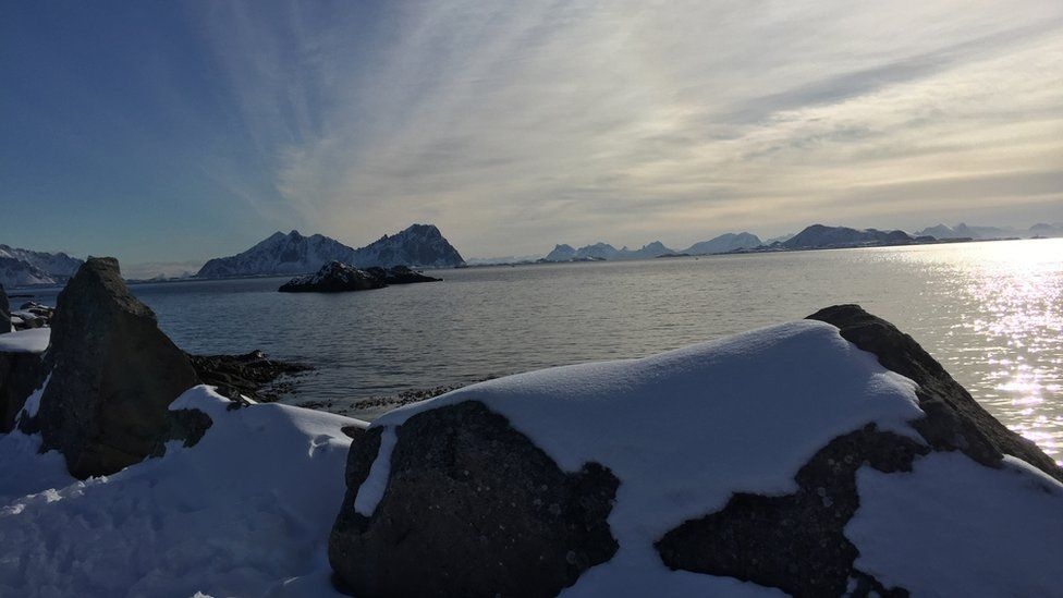 An open expanse of Norwegian water is seen over the tops of some snow-covered rocks