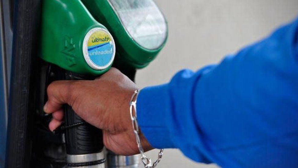A person uses a petrol pump in a BP filing station in Peckham, south London