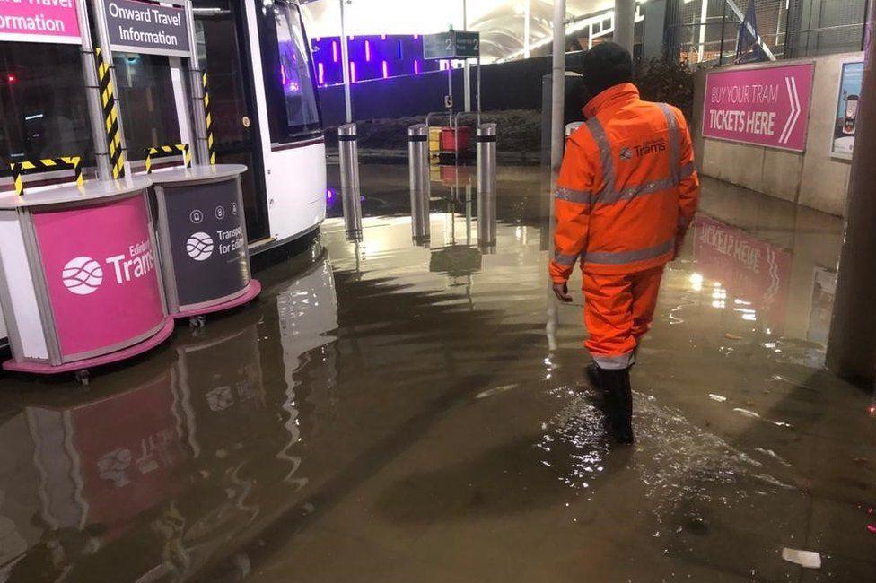 Worker at flooded tram station
