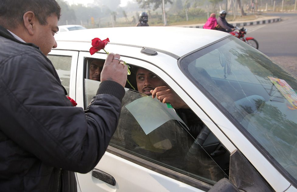 Indian civil defence volunteers distribute roses and urge commuters to stick to the rules