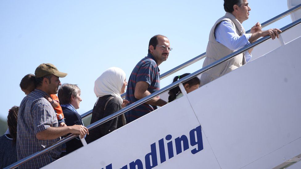 Migants board a plane bound for the Vatican