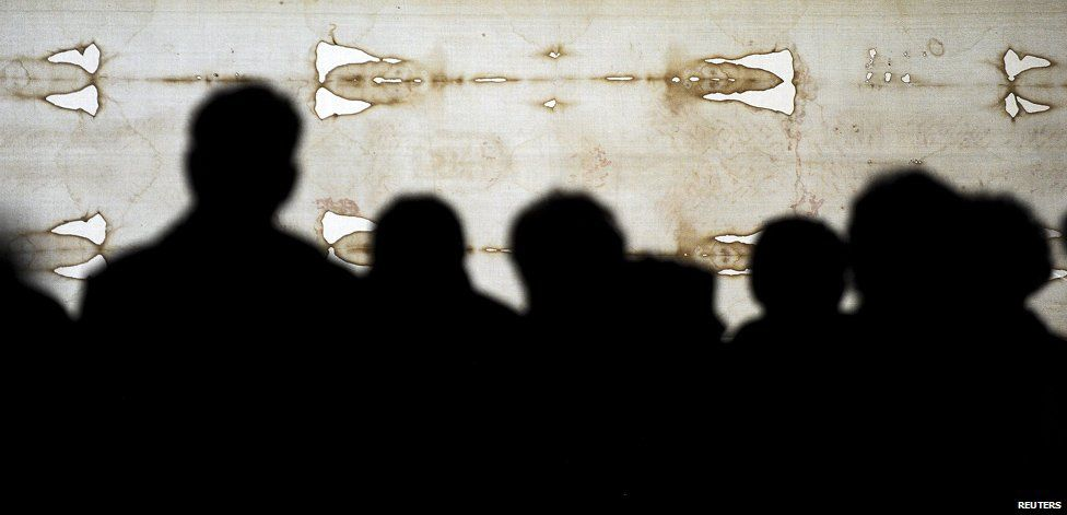 Faithfuls look at the Holy Shroud in the Cathedral of Turin during the opening day of the exposition April 19, 2015