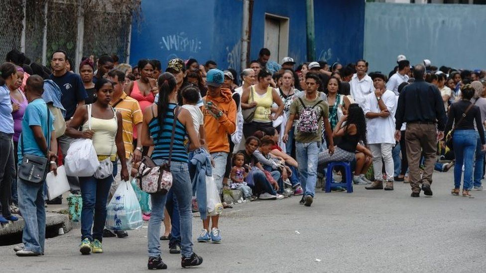 People queue to buy basic food and household items outside a supermarket in the Petare neighbourhood in Caracas, on June 1, 2016.