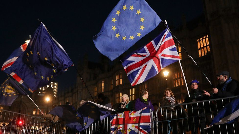 Anti-brexit campaigners wave Union and EU flags outside the Houses of Parliament in central London on December 12, 2018.