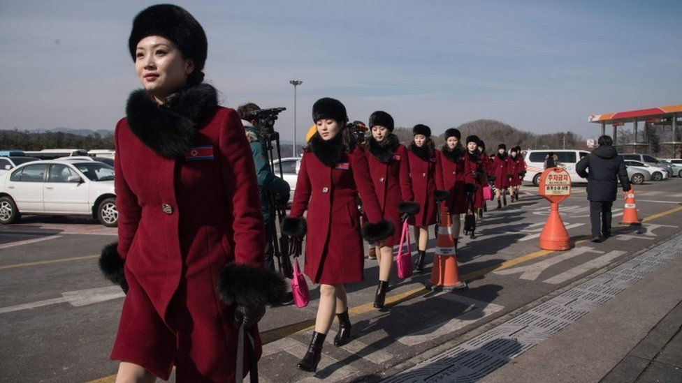 North Korean cheerleaders crossing car park after arriving as part of delegation