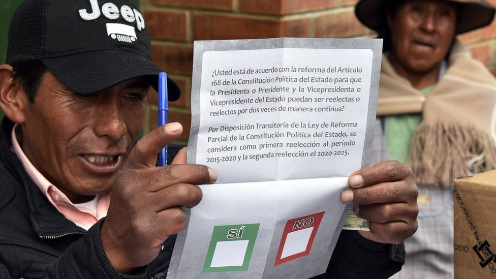 An election judge shows the ballot to a voter on February 21, 2016 in Huarina, 75 km from La Paz, Bolivia during a referendum on a constitutional reform that would allow Evo Morales to seek a fourth term as president, potentially extending his stay in office until 2025