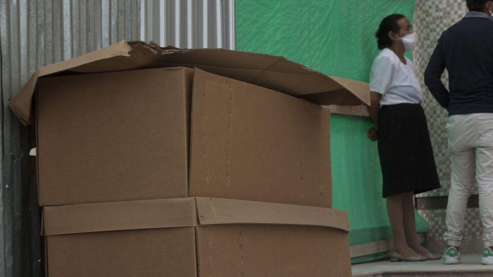 Cardboard coffins with bodies await outside Jardines de Esperanza cemetery in Guayaquil