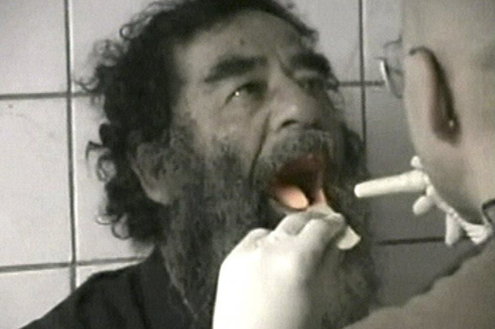 Saddam Hussein being examined after capture