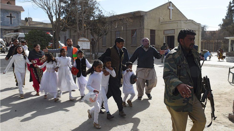 Pakistani Christian children wearing white are evacuated by security personnel from a Methodist church after a suicide bomber attack during a Sunday service in Quetta (December 17, 2017)