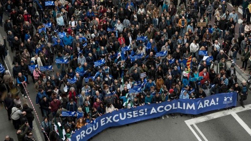 "Some of thousands of people hold a banner reading ""Enough excuses! Let's welcome now"" as they walk in a street of Barcelona (18 February 2017)"