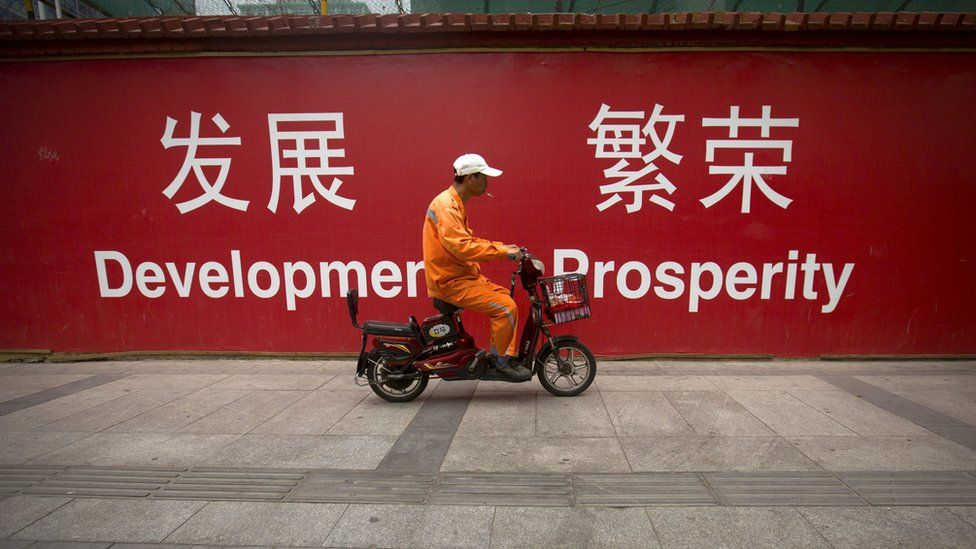 """A maintenance worker rides a scooter past banners reading """"Development"""" and """"Prosperity"""" in English and Chinese on a street in central Beijing"""