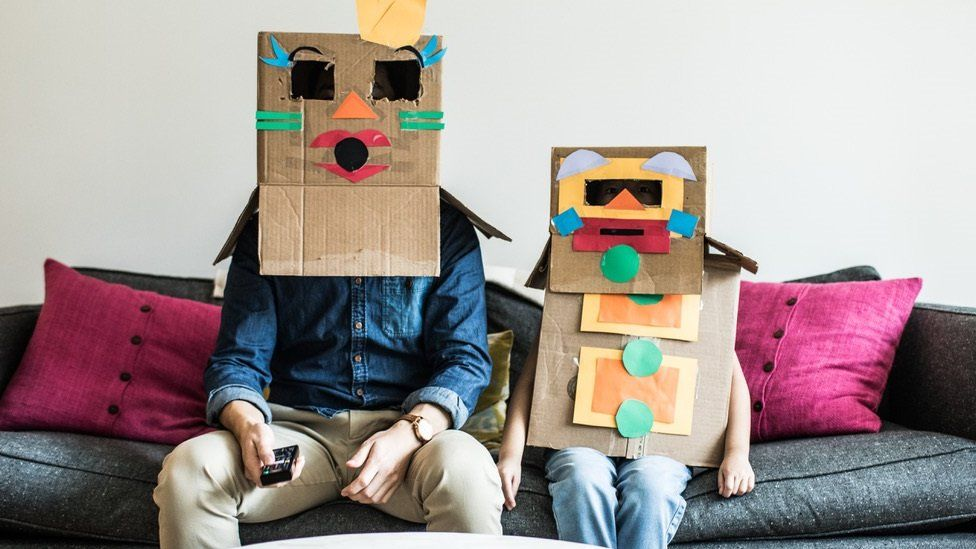 Man and child with boxes on their heads