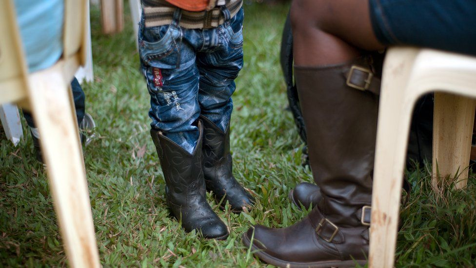 A toddler wearing cowboy boots in Kampala