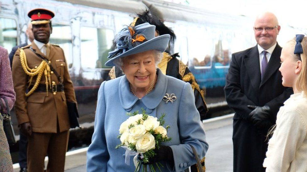 The Queen walking from a train
