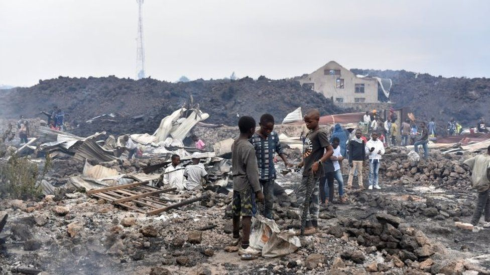 Residents pick up remains of their destroyed homes from the smouldering lava deposited by the eruption of Mount Nyiragongo volcano near Goma, in the Democratic Republic of Congo May 23, 2021