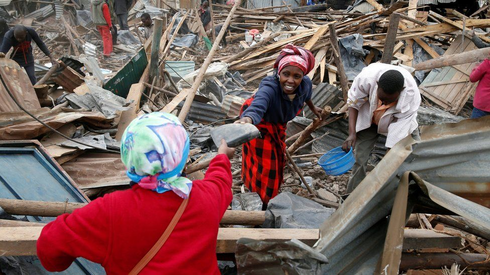 Catharine Kamiri (L) and her sister Mercy Wanjiku (C) collect the remainings of their belongings after bulldozers demolished their house to make way for a new road in the Kibera slum in Nairobi,