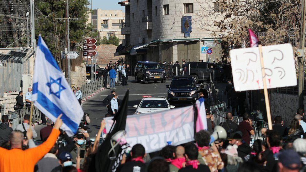 Protesters hold up placards and an Israeli flag as a convoy transporting Israeli Prime Minister Benjamin Netanyahu arrives at the Jerusalem District Court for a hearing on 8 February 2021