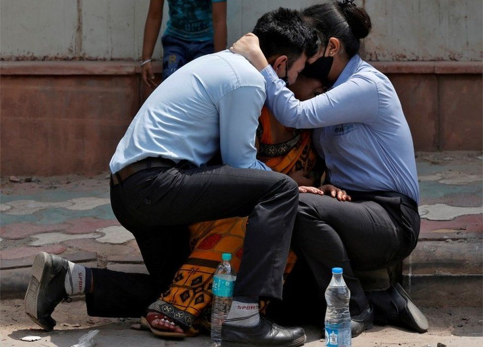 A woman is consoled by her children after her husband died from complications related to the coronavirus disease (COVID-19) outside a mortuary of a COVID-19 hospital in New Delhi, India, April 15, 2021.