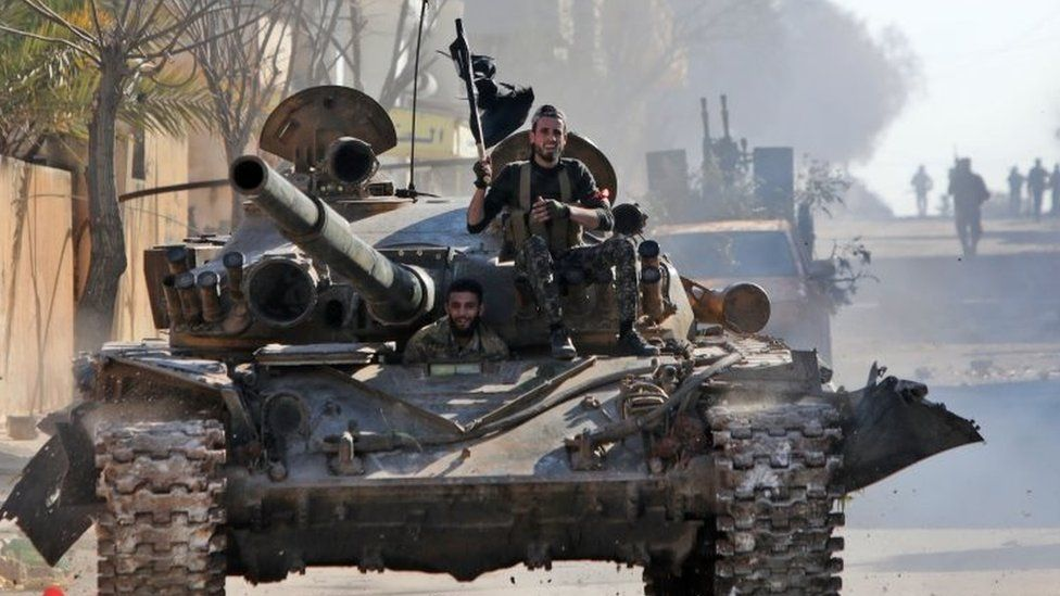 Turkey-backed Syrian fighters ride on a tank in the town of Saraqeb, Syria's Idlib province. Photo: 27 February 2020