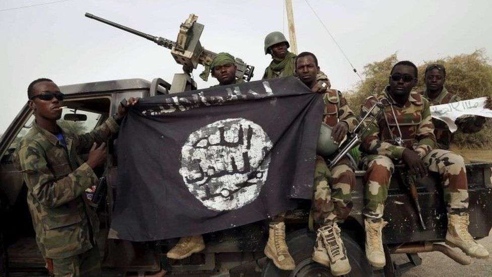 Nigerian soldiers holding up a Boko Haram flag captured in 2015