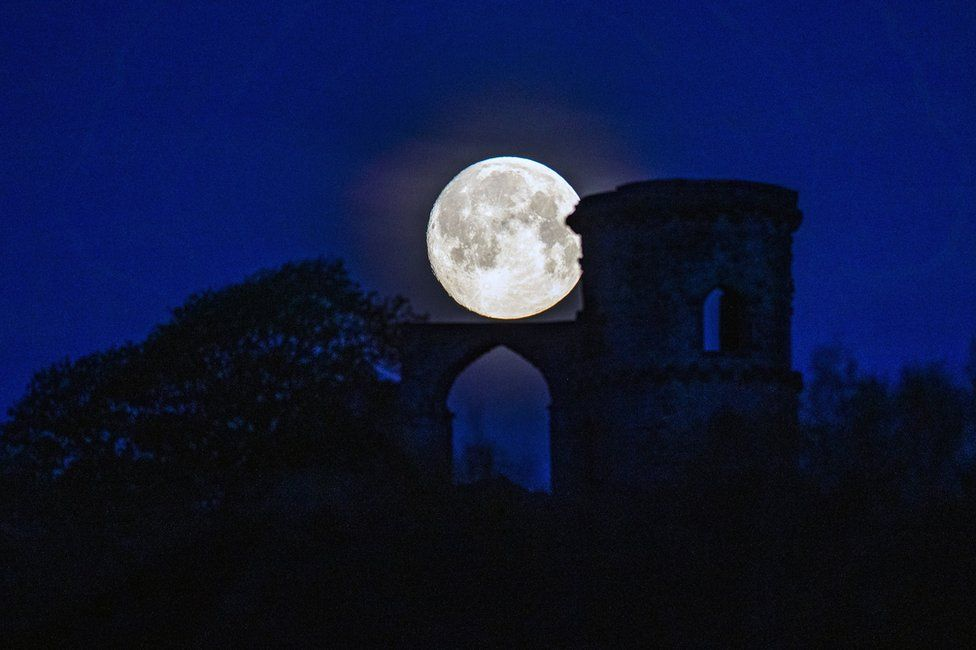 The pink supermoon seen against the silhouetted Mow Cop Folly in Cheshire, UK