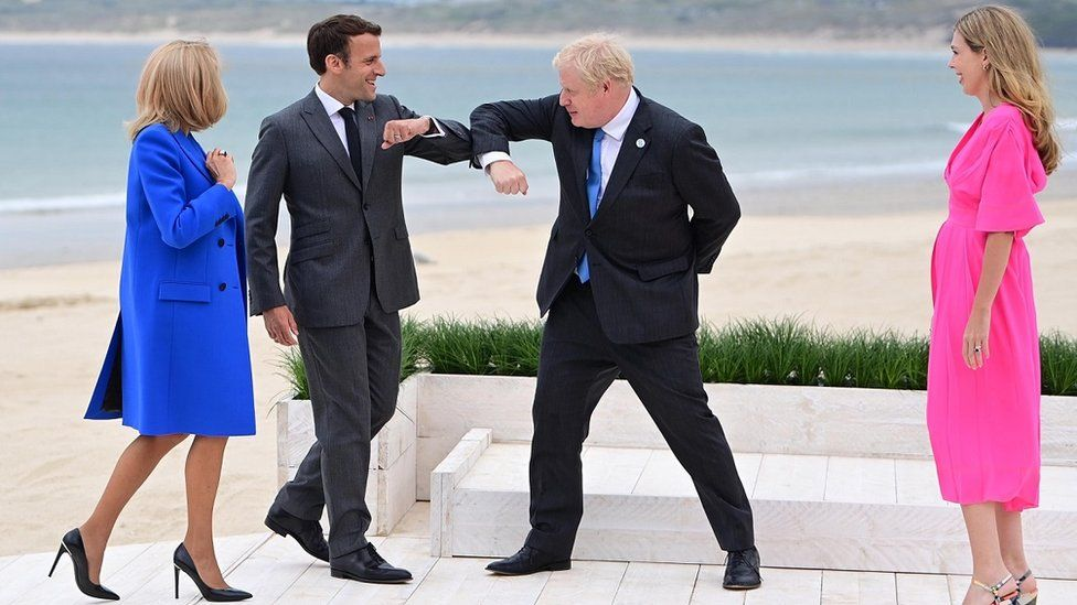 France's President Emmanuel Macron (centre L) greets Prime Minister Boris Johnson (centre R) at the official leaders welcome during the G7 summit