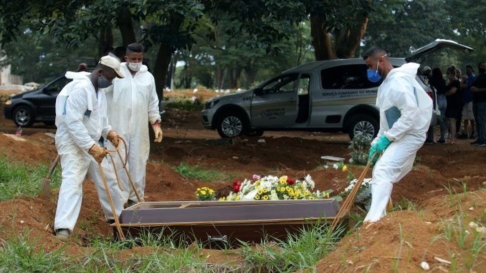 Gravediggers wear protective suits as they work during a burial
