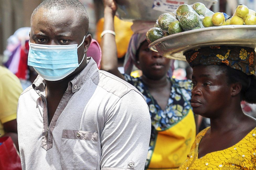 A man in a face mask walking through a market in Accra, Ghana- Saturday 14 March 2020